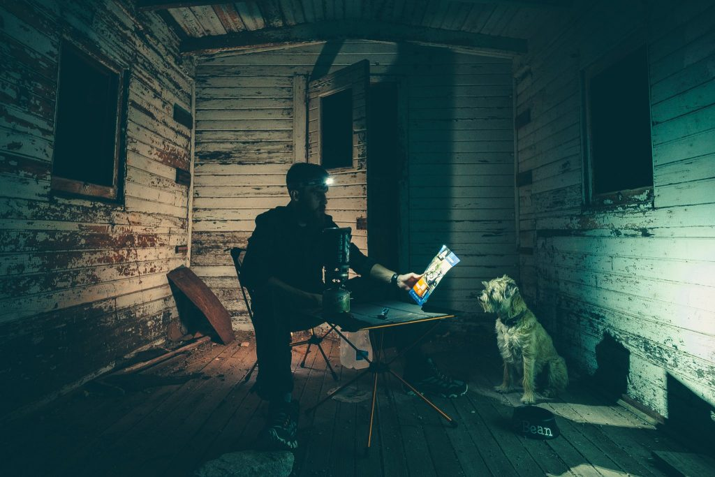 person sitting in abandoned house in dark with headlamp shining on pouch of Mountain House