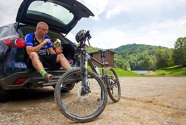 man enjoying mountain house freeze dried food after long mountain bike trek