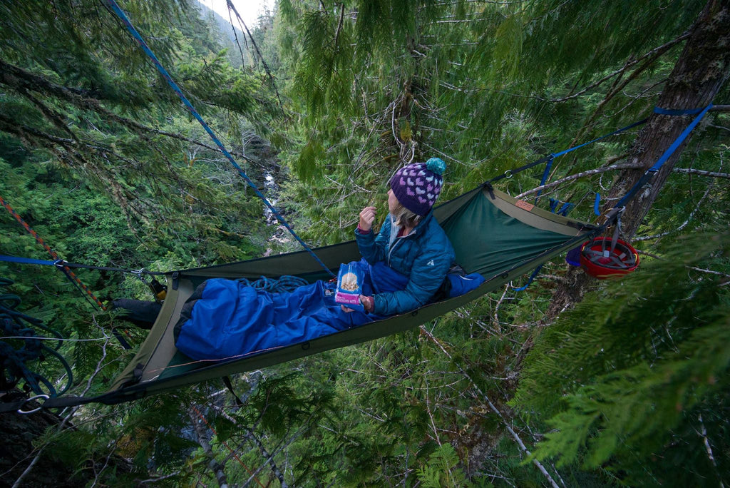 Kelli Martinelli eating freeze-dried cheesecake bits while in hammock up high in trees