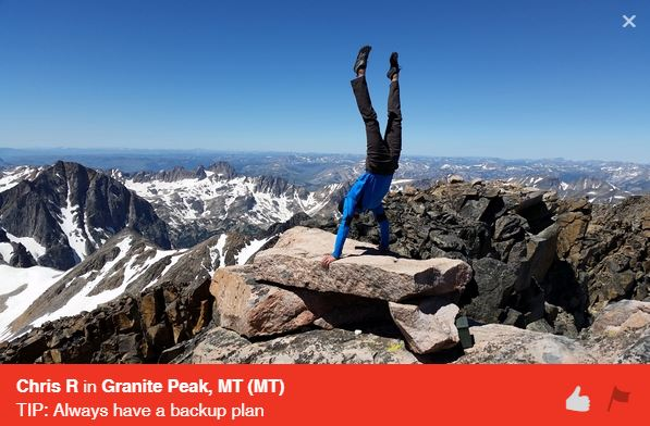 person doing handstand on rock boulder on top of mountain