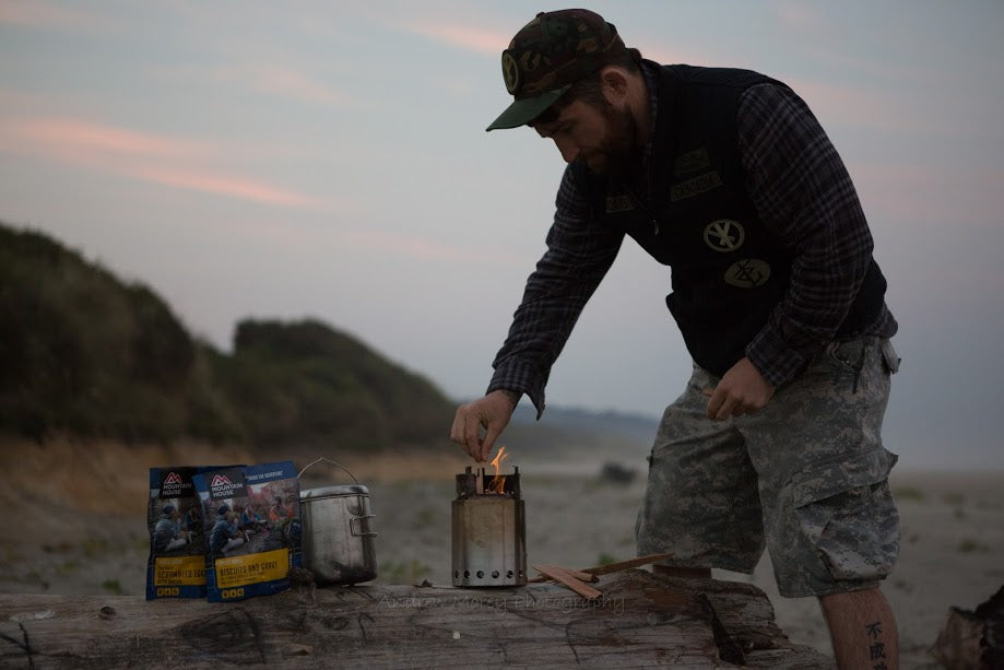 person lighting a tinder stove on a beach log with pouches of Mountain House close by