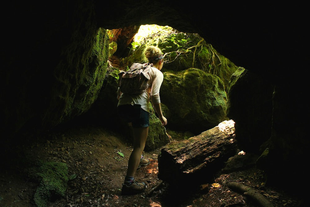 Woman ducking through cave exit at Florida Caverns State Park in Marianna, FL
