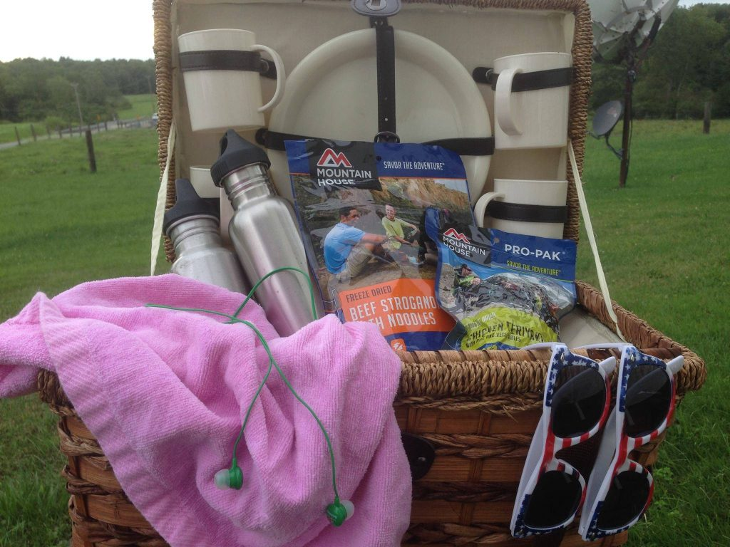 Open picnic basket containing mugs, blats, steel bottle containers, (1) Mountain House Beef Stroganoff pouch, (1) Mountain House Chicken Teriyaki vacuum sealed Pro-Pak pouch, with (2) American flag styled sunglasses hanging on edge of picnic basket, along with a pink blanket and a pair of green headphones.