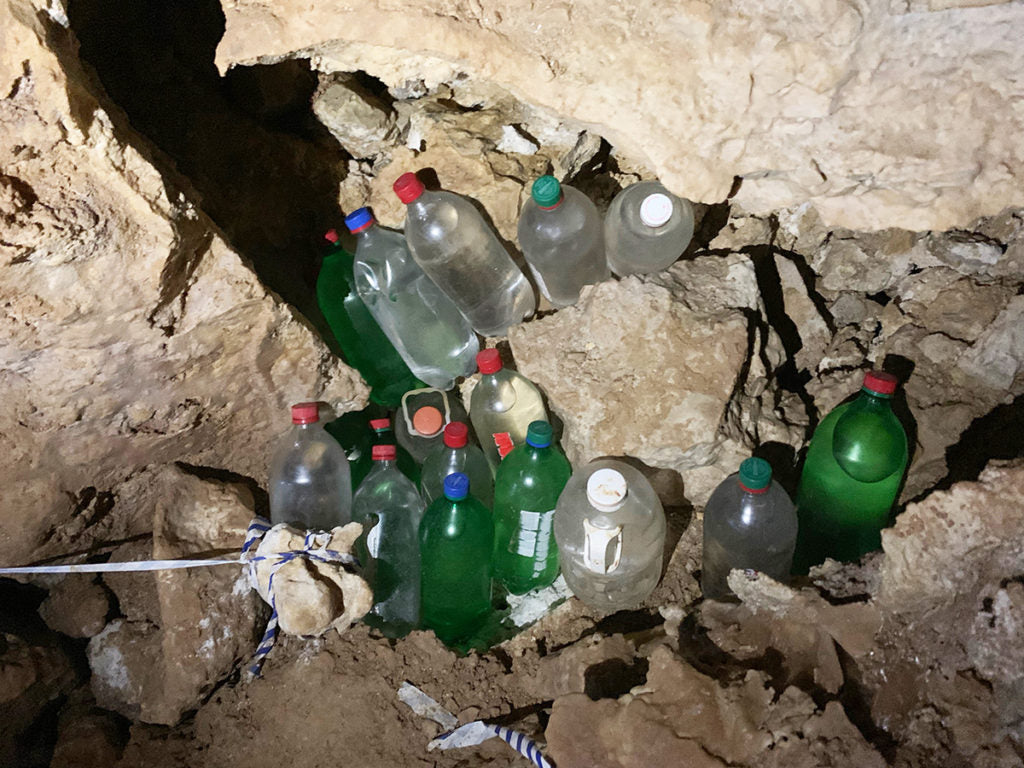 A cache of re-used 2-liter bottles filled with clean water tucked in amongst the rocky crevices of a cave. Photo credit John Waller/Uncage the Soul Productions.