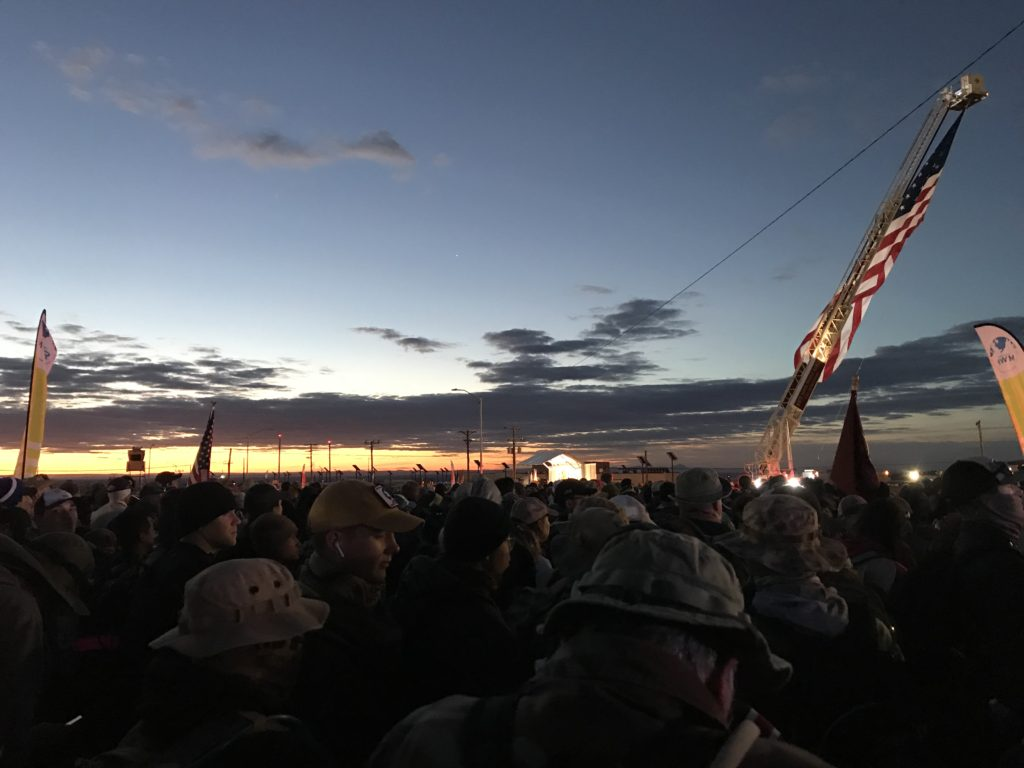 Hundreds of marchers standing under American flag at dusk