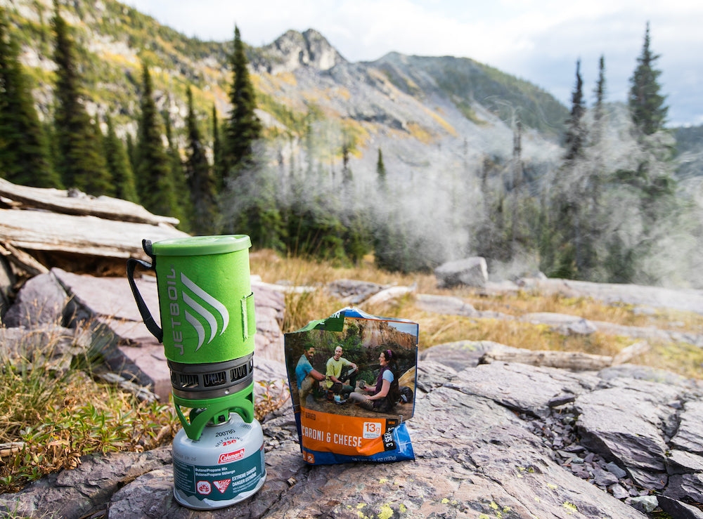 A steaming Jetboil and a pouch of Mountain House Mac and Cheese on a rocky mountain top.