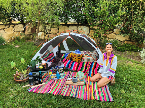 A smiling woman sits on a colorful blanket in front of a tent on a lawn, with a picnic spread.
