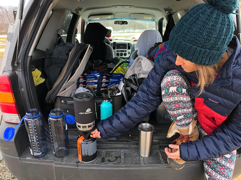 A woman sits on the back of an open tailgate with a Jetboil and two Nalgene bottles.