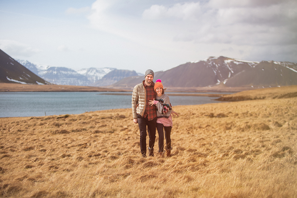 A smiling couple wearing beanies walks toward the camera with mountains and a lake behind them.