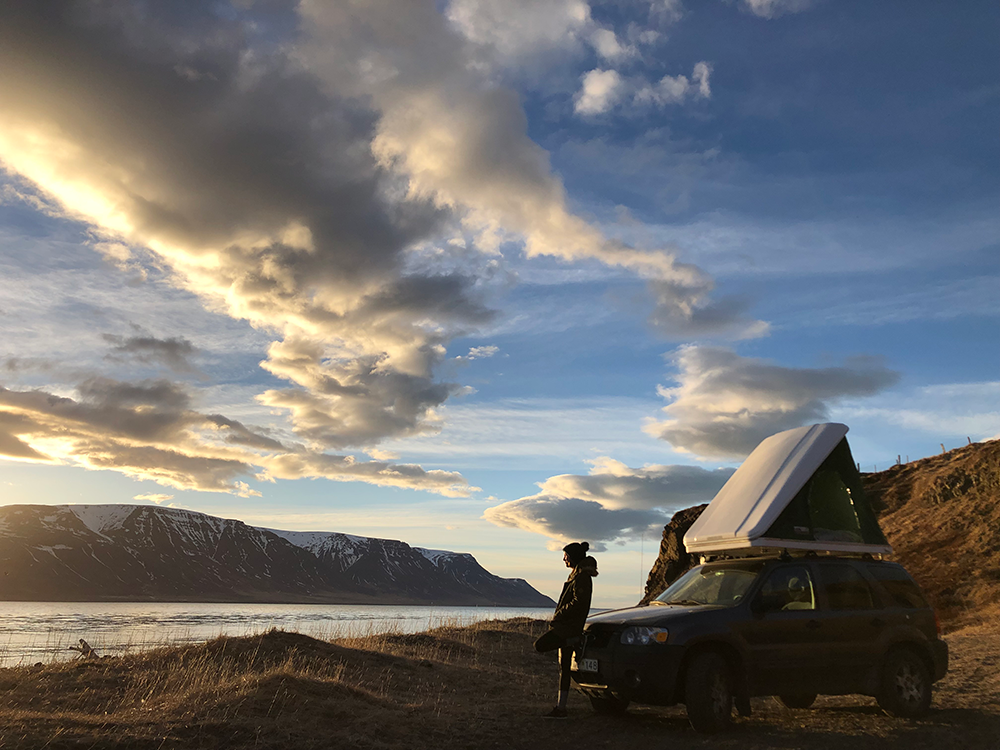 A person leans against the front of a car that has a pop up tent on top, clouds and a lake are in the distance.