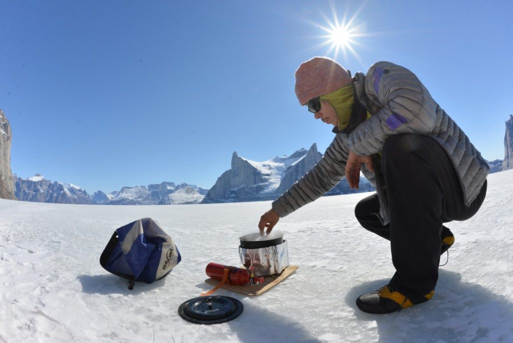 person using liquid fuel stove on snow