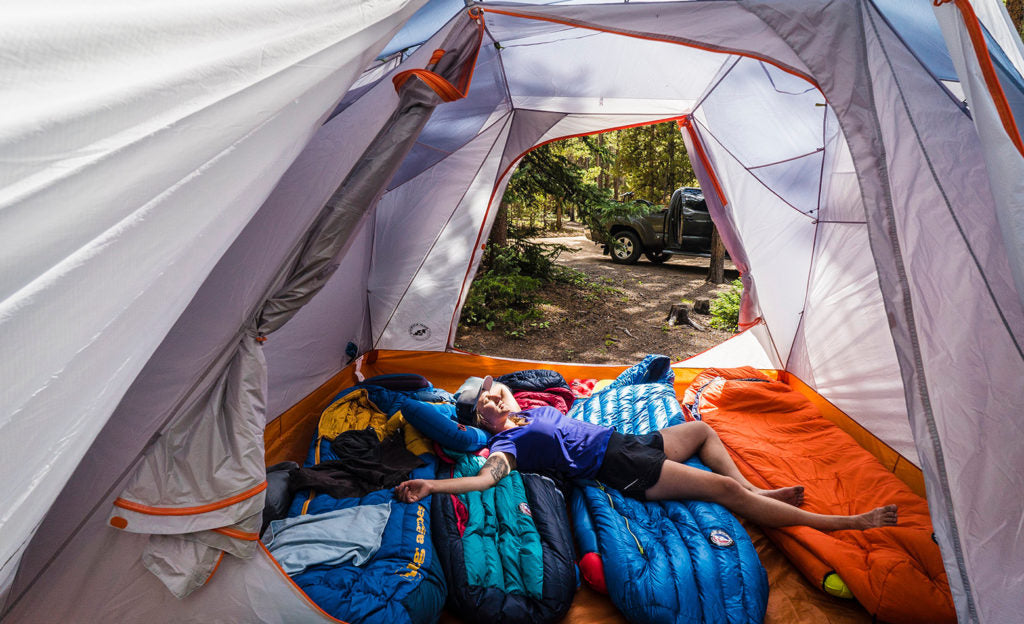 A person is sprawled out in an open tent on top of several sleeping bags.