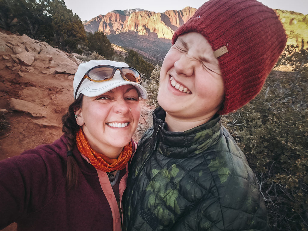 A photo of the author in a white ball cap and sunglasses and her tall teenage son with a mountainous backdrop behind them.