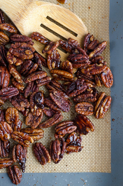 wooden spoon and spiced roasted pecans on table cloth