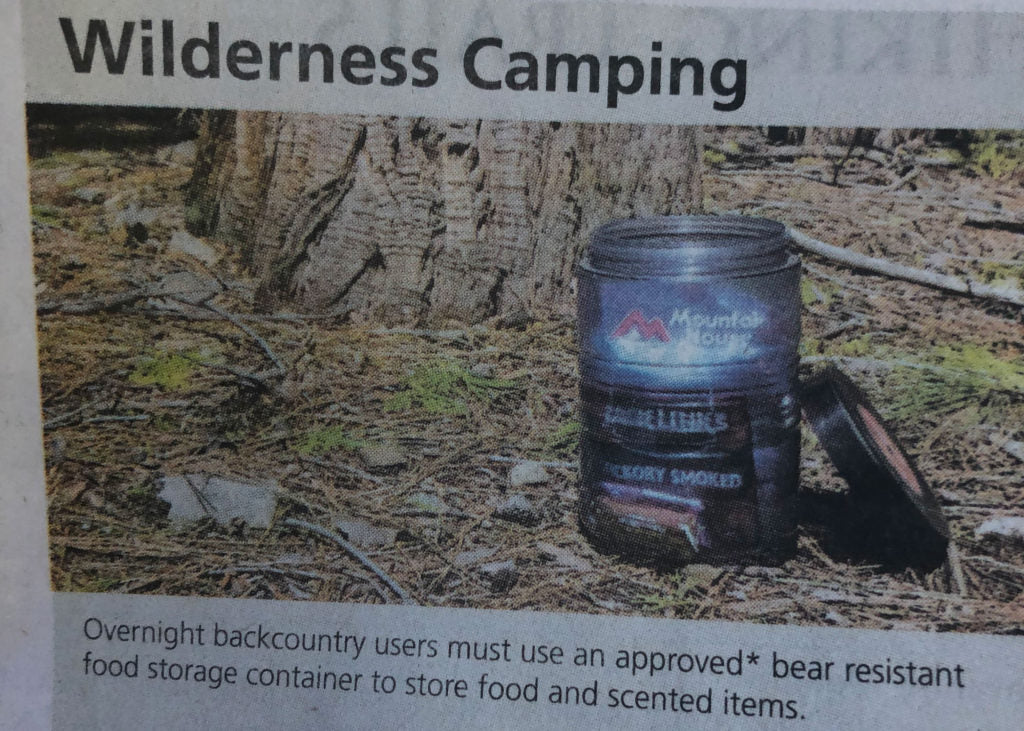 Magazine clipping showing mountain house and sausage links in bear resistant food storage container
