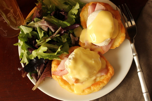 eggs benedict next to spring leaf salad on white plate