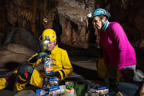 Phyliss overlooks shoulder of man in cave stirring food in Mountain House pouch