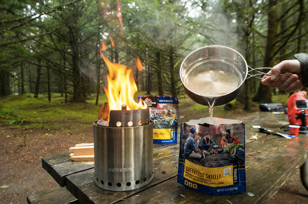 person pouring boiling water in Breakfast Skillet Mountain House pouch on camp picnic table
