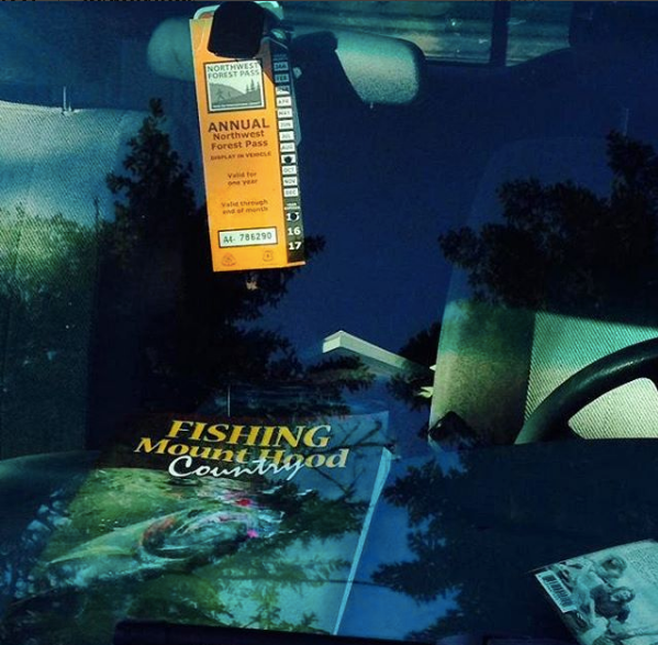view from looking inside front window of car with nw forest pass hanging from car mirror with fishing Mountain Hood Country magazine on dashboard