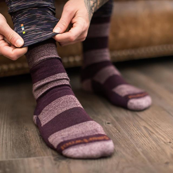 person pulling pants over purple striped smartwool socks