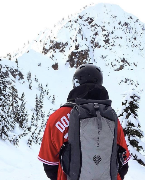 back view of person wearing aqua quest backpack staring at snow covered mountain