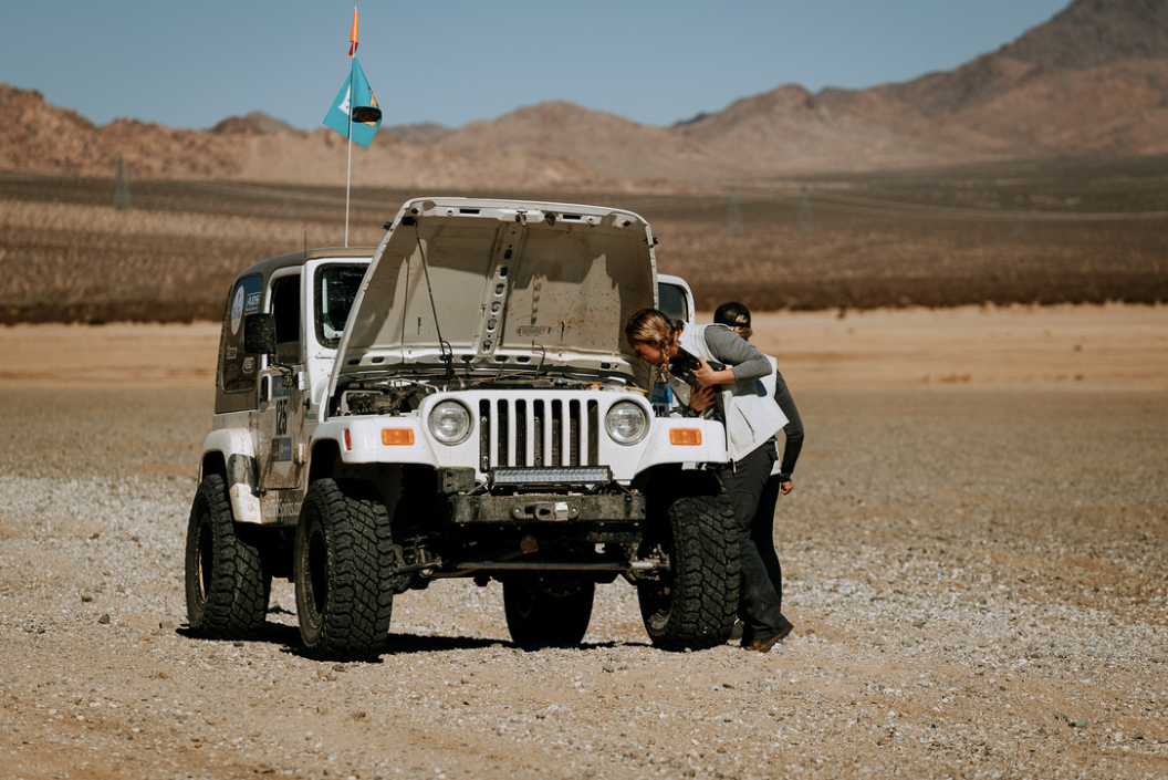 White jeep with hood open.