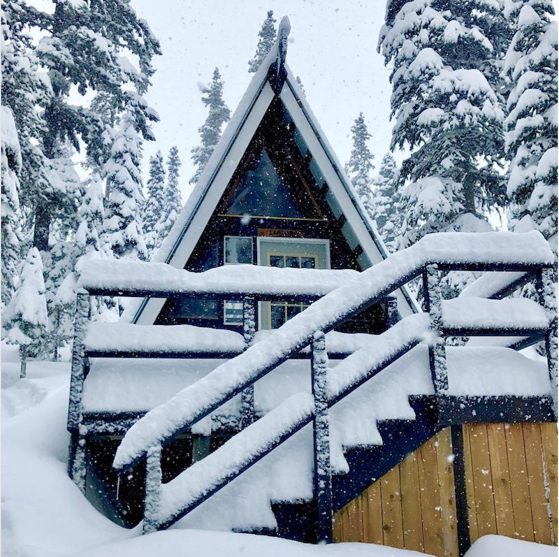 A-frame cabin covered in snow