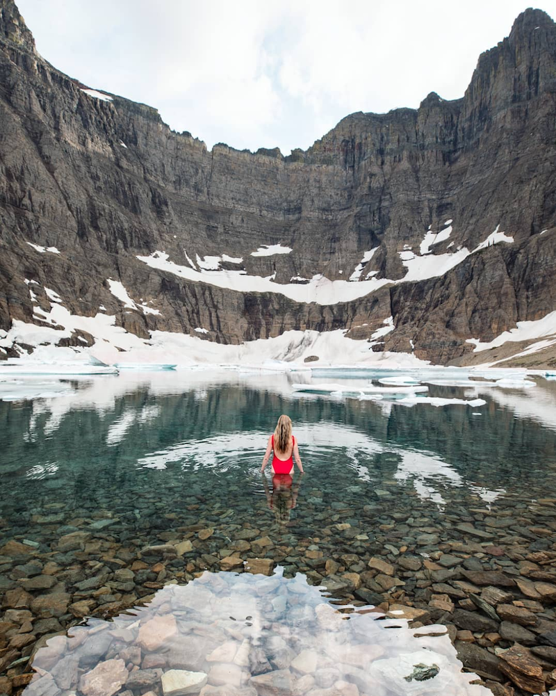 Girl in red bathing suit standing past knees in mountain lake with snow on mountain