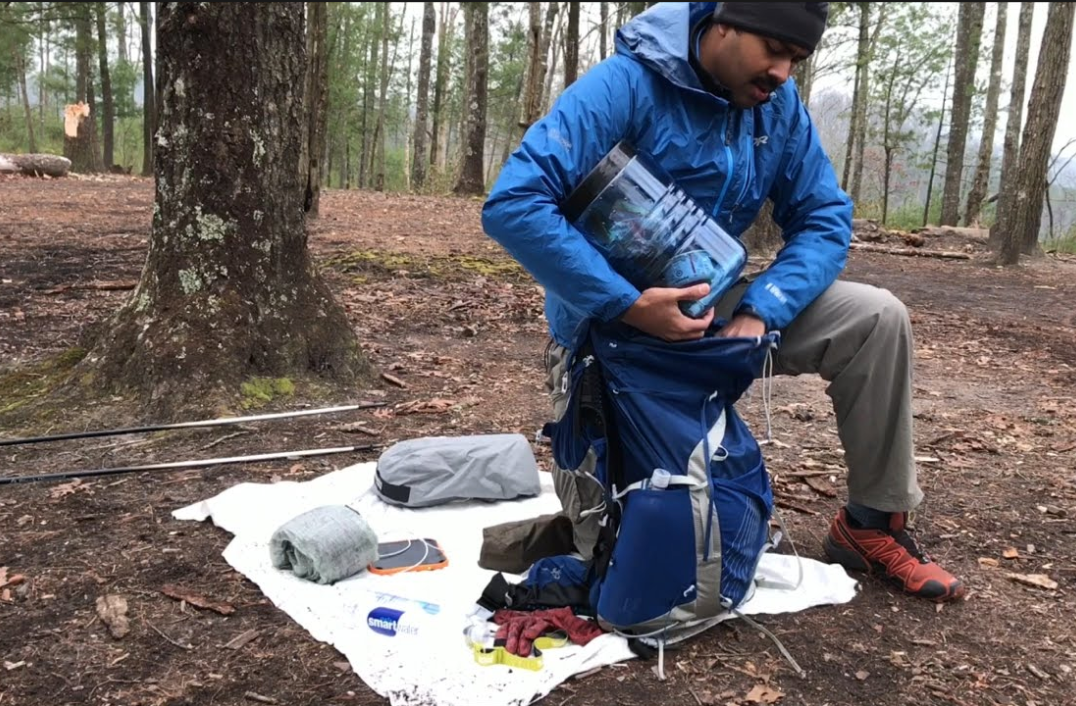 Man loading hiking pack with bear canister