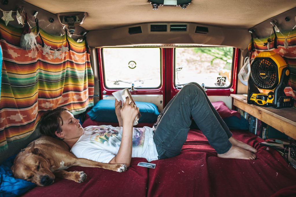 A teen rests in the back of a van with his dog, while reading a book.