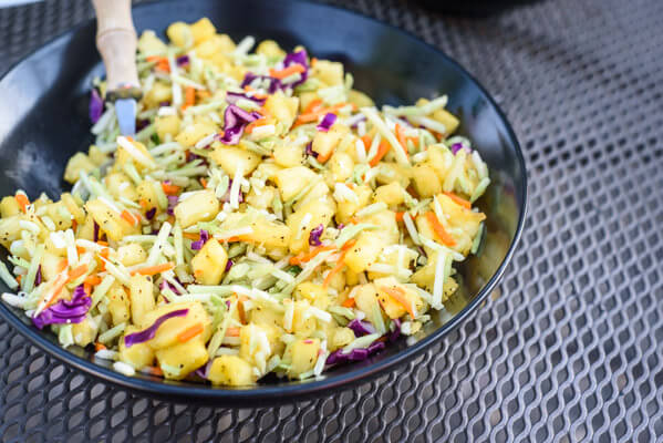 black bowl of Asian broccoli slaw with pineapple