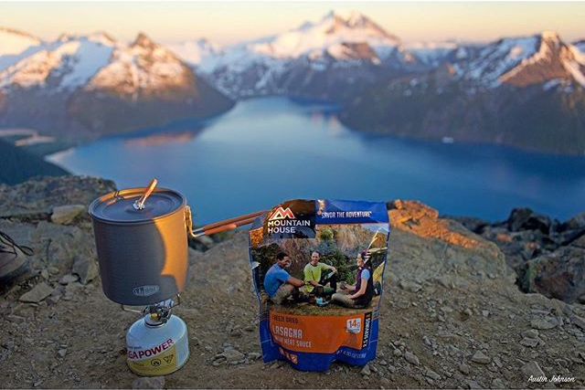 pouch of Mountain House Lasagna next to camp stove on top of rocky mountain peak with view of lake and snow covered mountains in background
