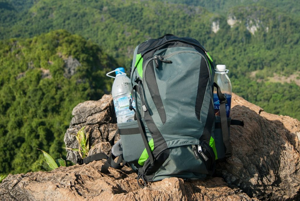A small daypack carries a water bottle on each side.