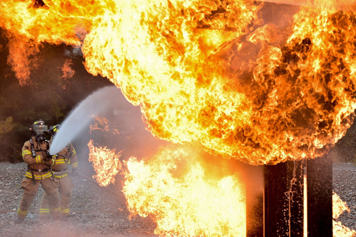 firefighters spray water hose onto flames