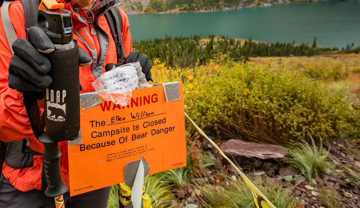 Person holding bear spray stopped at warning sign by a lake that says the campsite is closed due to bear danger.