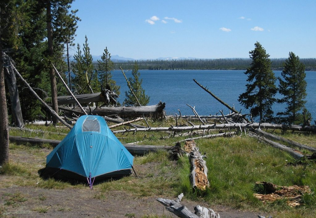 Blue camping tent at campsite by lake.