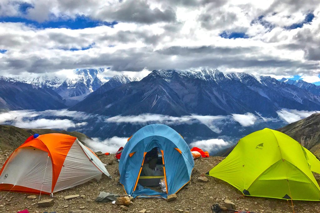 3 camping tents on snowcapped mountain peak.