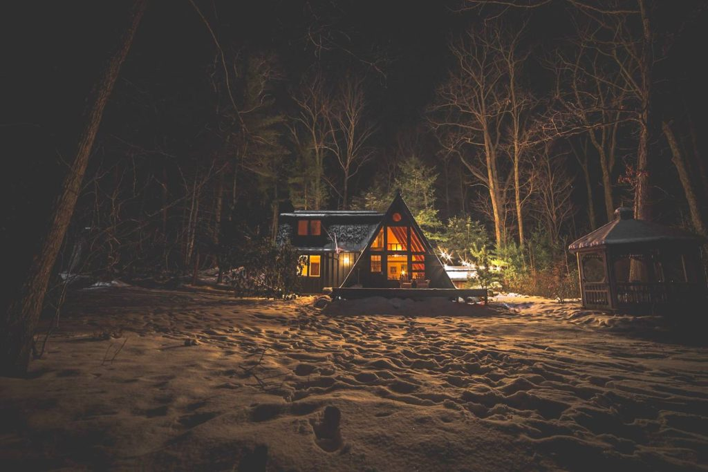 A-frame lit from within at night with snow on the ground outside.