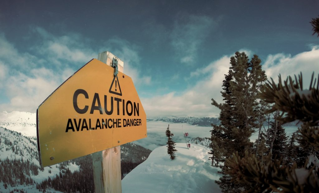 Avalanche Danger caution sign on snowy mountain slope.