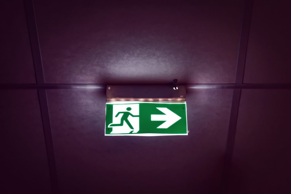 Escape route sign on ceiling pointing right.
