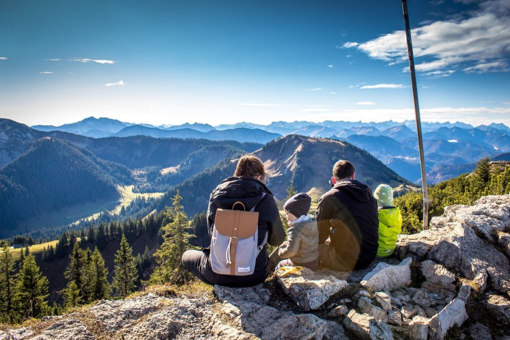 Family sits on mountain overlook.