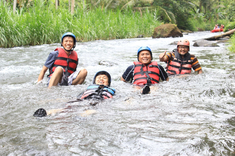 4 family members wearing life jackets laugh, sitting in shallow river.