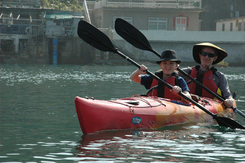 Father & son double kayak in harbor.