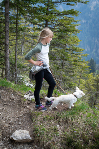 Girl with small dog on trail.