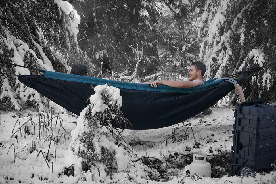 two eople sitting in blue hammock hot tub in snow covered forest