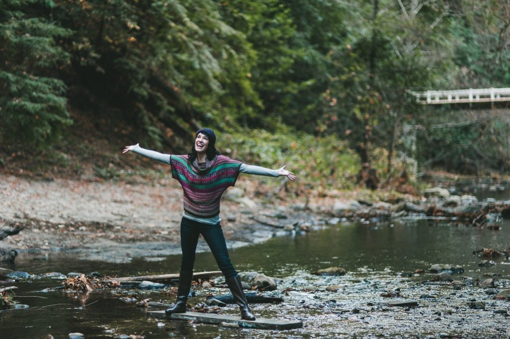 Smiling woman spreads arms in river stream.