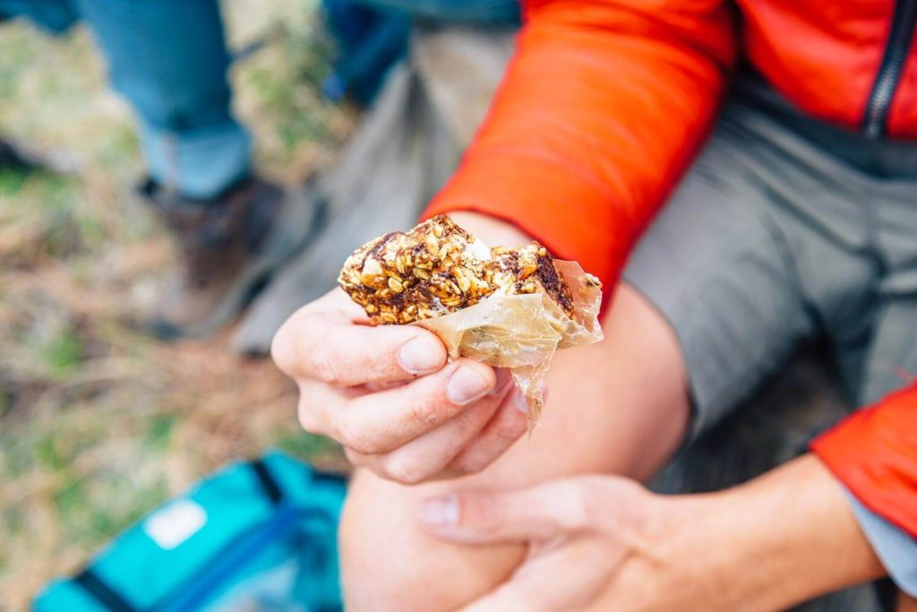 a homemade granola bar wrapped in wax paper in someone's hand