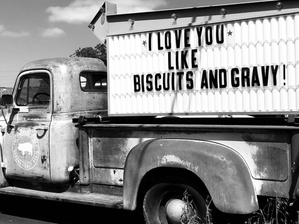 "Vintage pickup truck with a sign in the bed that says ""I Love You Like Biscuits And Gravy!"""