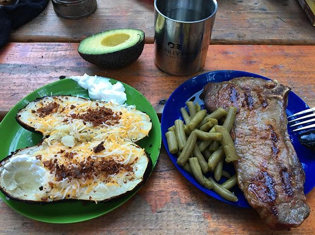 Green plate of fully loaded backed potatoes on table next to blue plate of steak and green beans. Behind plates is a open faced avacado and cup of water