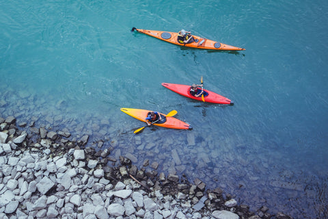 3 sea kayakers paddle by rocky shoreline.